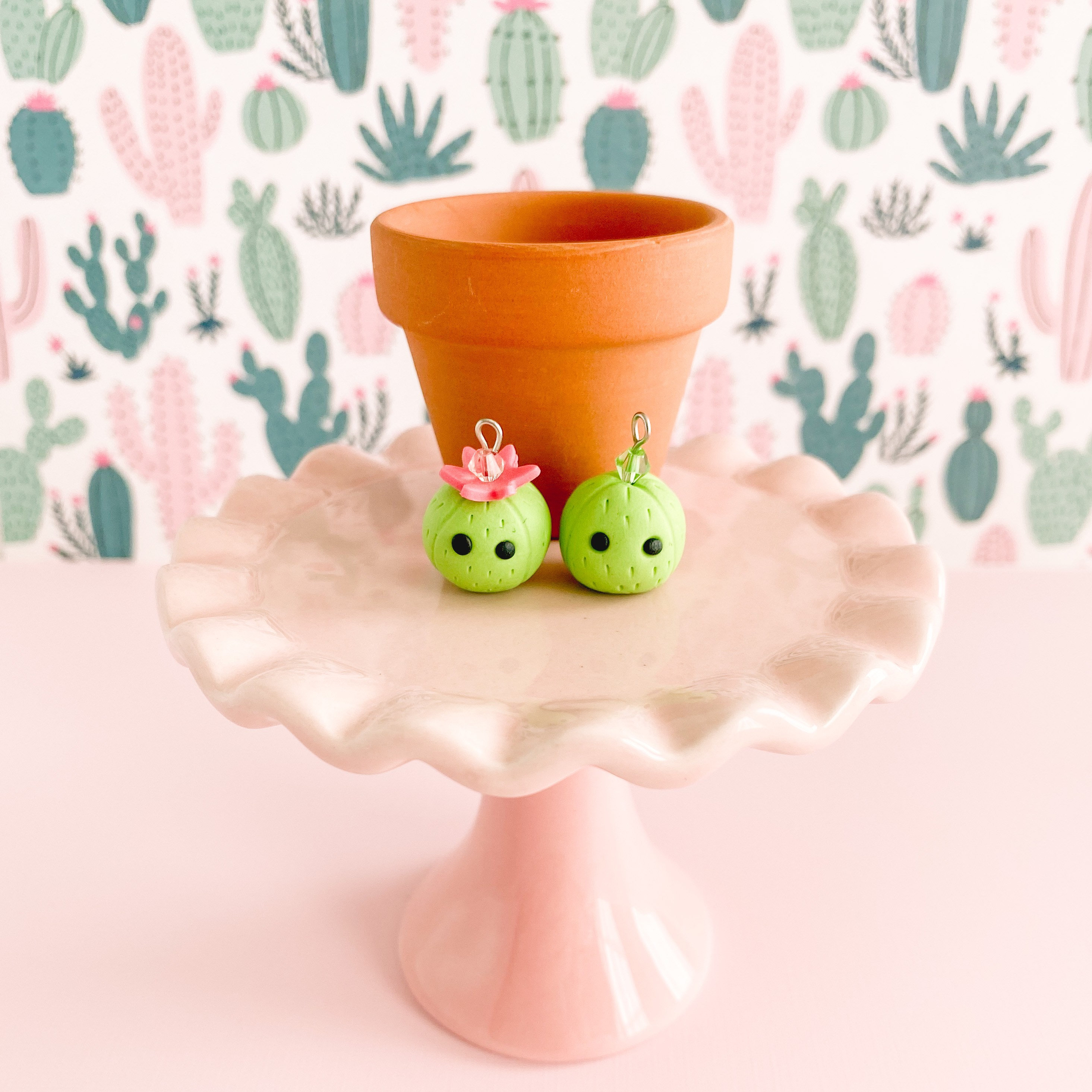 fireflyFrippery Cute Cactus Charms in front of Miniature Terra Cotta Pot on Pink Display