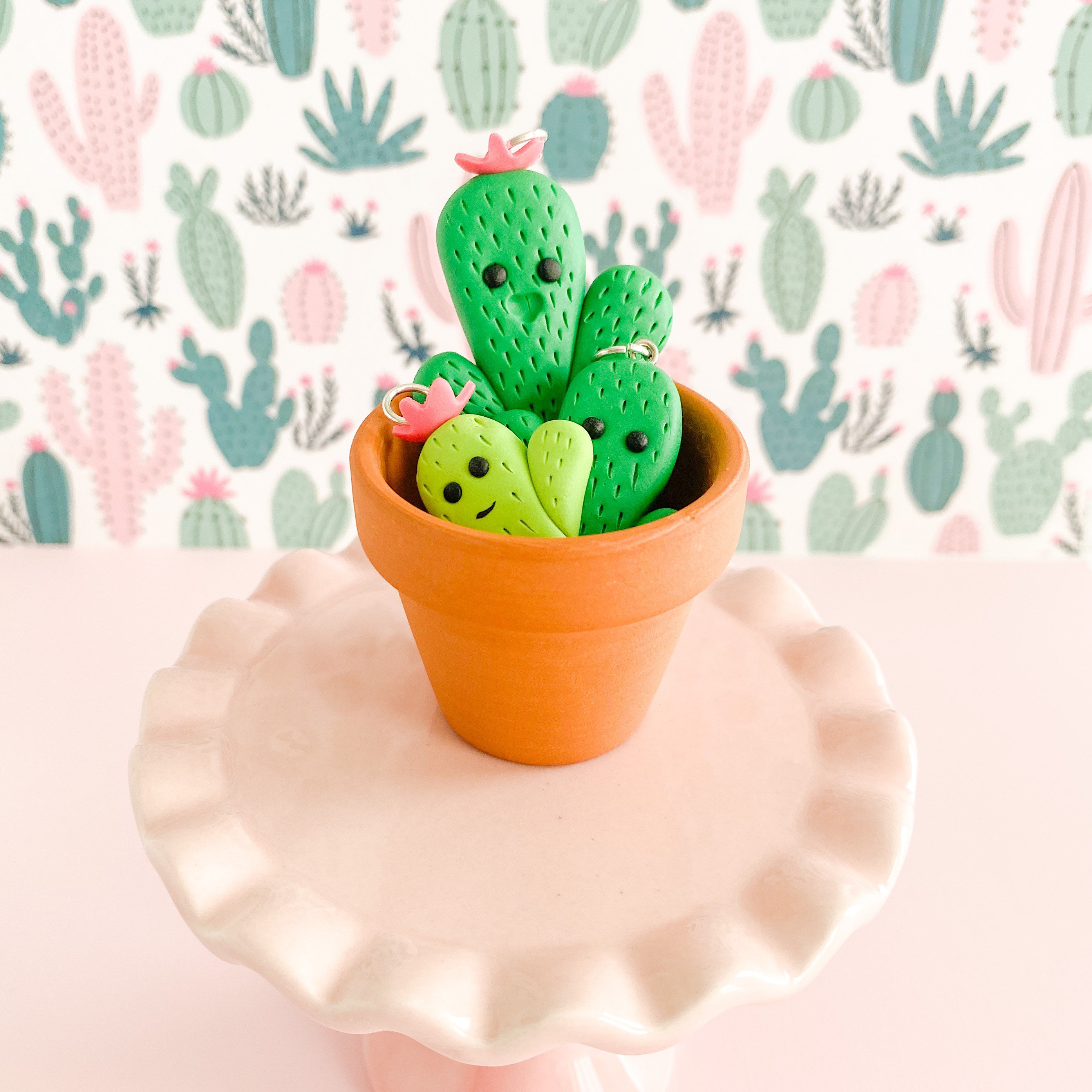 fireflyFrippery Kawaii Cactus Charms in Miniature Terra Cotta Pot on Pink Display