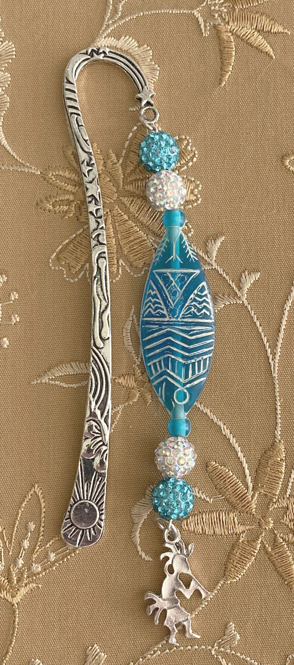 Stunning bookmark based on Native American deity Kokopelli who was also a flutist.  Sheperd hook is very well made and embellished.  The pendant has the look of Native American etcting.  Two beads one in bright blue and other is white has a great texture. At very bottom is a charm of Kokopelli.
